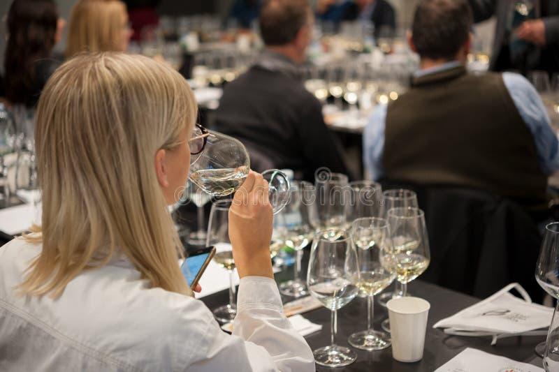 Mensen die witte wijn proeven en nota's maken bij degustationkaart royalty-vrije stock foto