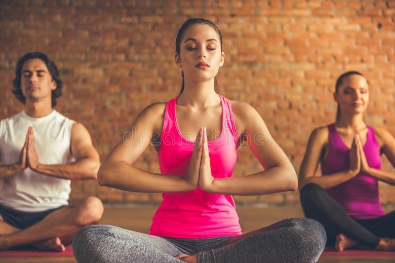 Mensen die Yoga doen stock fotografie
