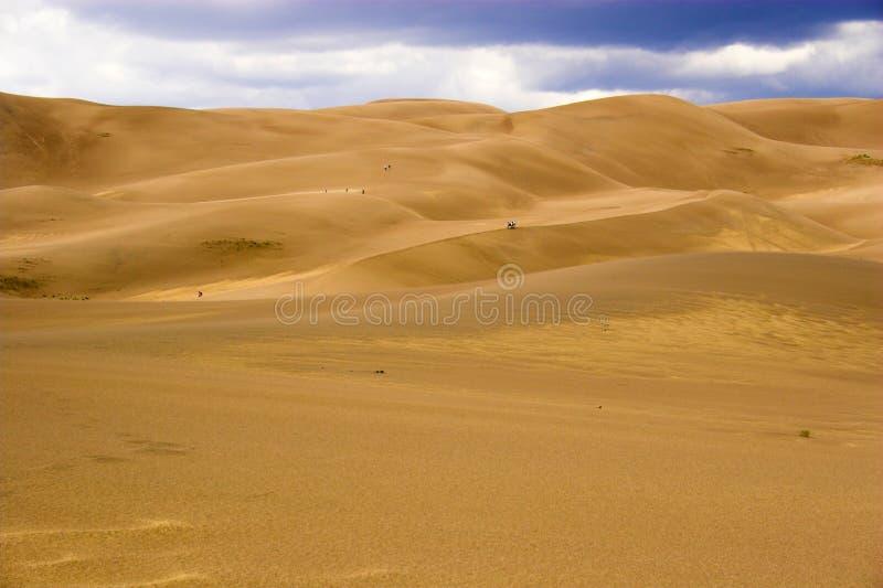 Mensen die in zandduinen lopen stock foto