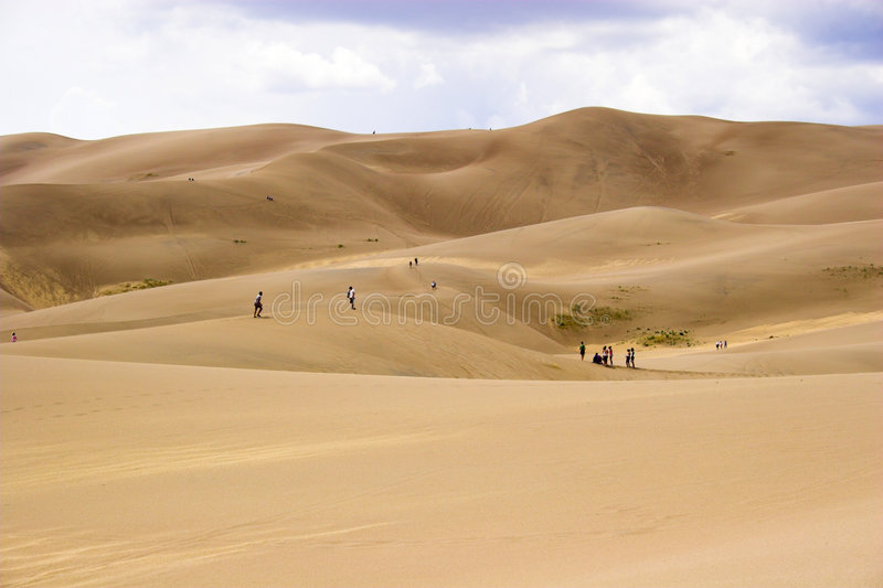 Mensen die in zandduinen lopen stock afbeeldingen