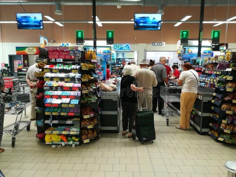 Mensen die zich bij rij bij de supermarkt bevinden royalty-vrije stock afbeeldingen