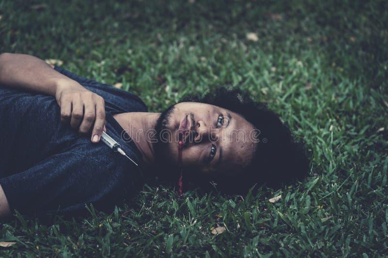 Mensen dood op het gras en het aftappen van de mond na het inspuiten van teveel Concept drugsverslaving en overdosis stock afbeelding