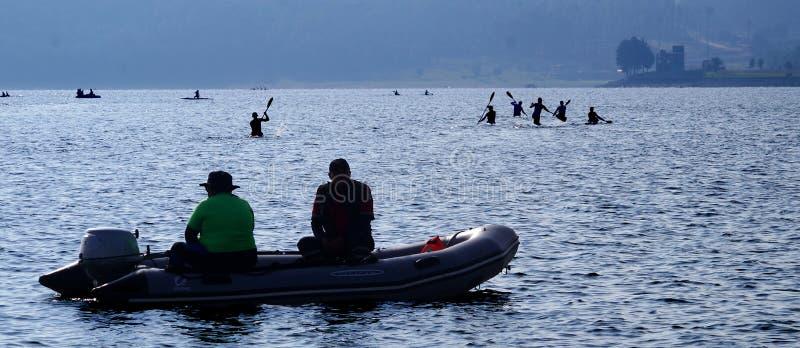 Mensen in een boot en roeiers stock afbeeldingen