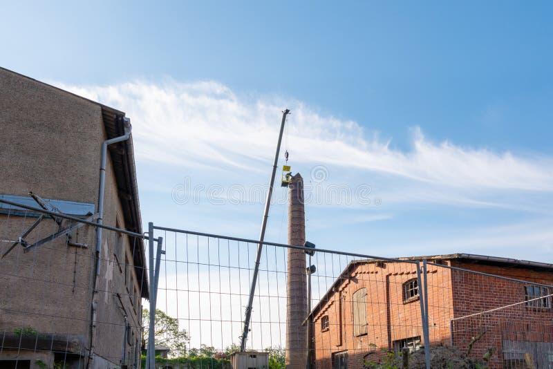 Mensen in een mand die van een gigantische kraan hangen die, nauwgezet een fabrieksschoorsteen verwijderen royalty-vrije stock foto