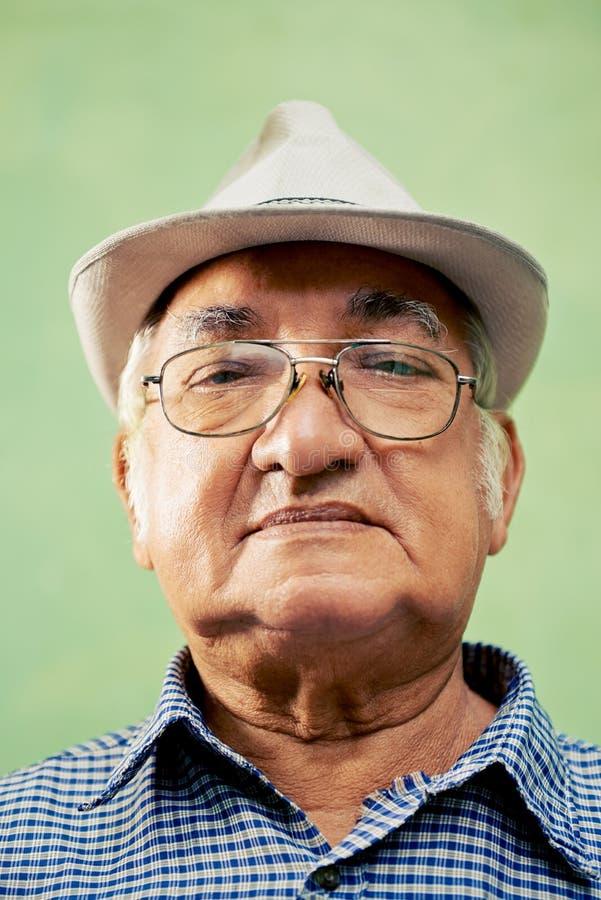 Portret van de ernstige oude mens die met hoed camera bekijken royalty-vrije stock afbeelding