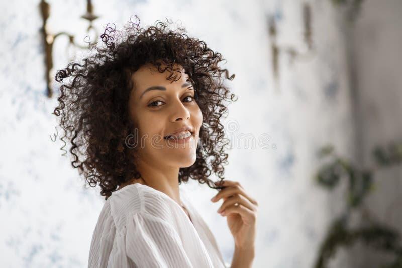 Mensen en gelukconcept Vrolijke Afrikaanse Amerikaanse jonge vrouw die bij camera glimlachen die haar ultrawhitetanden met steune royalty-vrije stock foto's