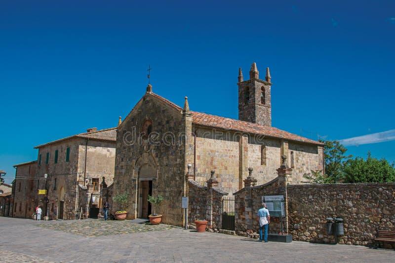Mensen en kerk bij het gehucht van Monteriggioni stock fotografie