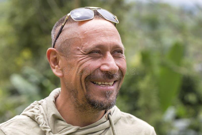 Mensen en levensstijlconcept Gelukkige ongeschoren mens op middelbare leeftijd met vrolijke glimlach openlucht tegen groene aarda royalty-vrije stock foto's