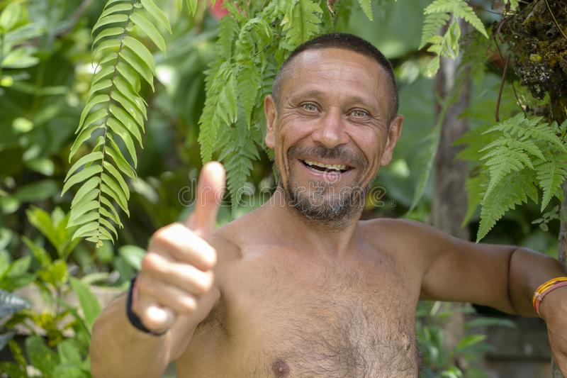 Mensen en levensstijlconcept Gelukkige ongeschoren mens op middelbare leeftijd met vrolijke glimlach openlucht tegen groene aarda royalty-vrije stock foto