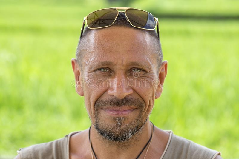 Mensen en levensstijlconcept Gelukkige ongeschoren mens op middelbare leeftijd openlucht tegen groene aardachtergrond, portret di stock afbeeldingen