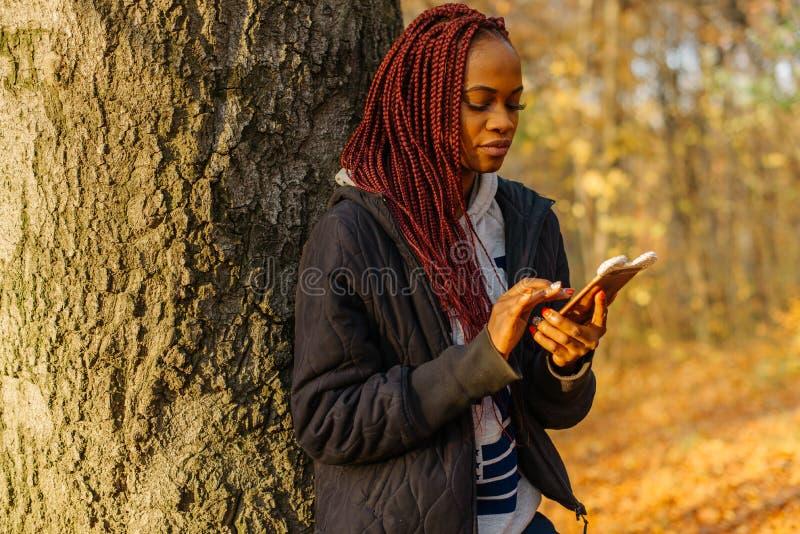 Mensen en Technologie De aanbiddelijke jonge Afrikaanse vrouw met rood haar babbelt en doorbladert op de mobiele telefoon terwijl stock foto