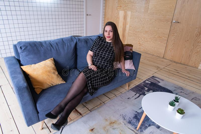 Mensen en vrije tijdsconcept - gelukkige jonge vrouw plus groottezitting op bank thuis royalty-vrije stock afbeeldingen