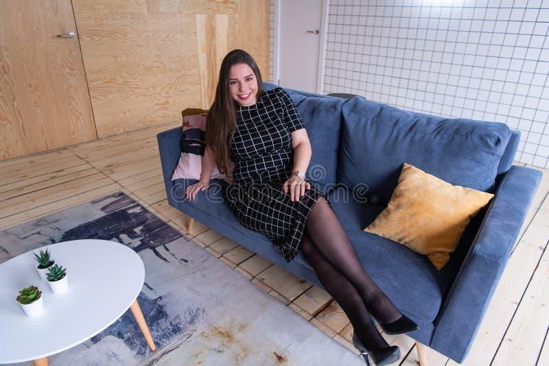 Mensen en vrije tijdsconcept - gelukkige jonge vrouw plus groottezitting op bank thuis stock foto's