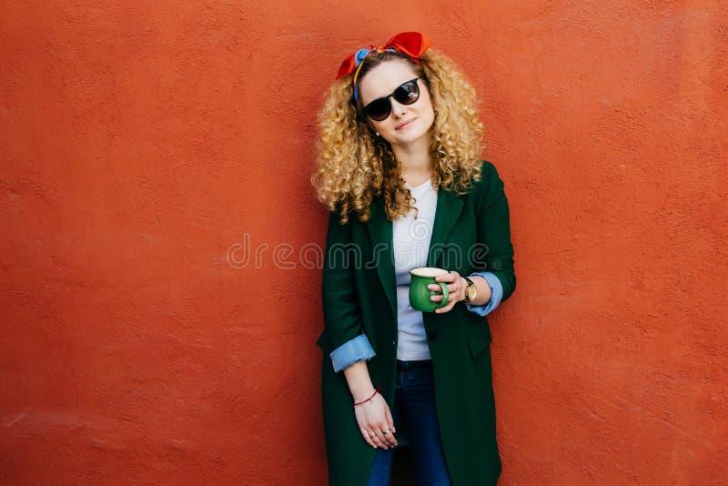Mensen en vrije tijdsconcept Horizontaal portret van mooi meisje die hoofdband, jasje, jeans en zonnebril dragen die kop van hete stock afbeelding