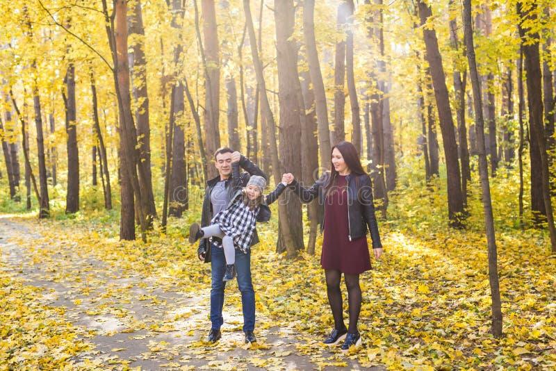 Mensen, familie en vrije tijdsconcept - de gemengde de rasvader en moeder hebben pret in de herfstpark met hun dochter stock fotografie