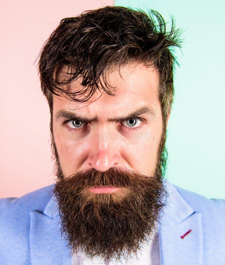 Mensen gebaarde hipster op strikte gezichts roze blauwe achtergrond Hipsterkerel met slordig slonzig haar en de lange kapper van  royalty-vrije stock fotografie