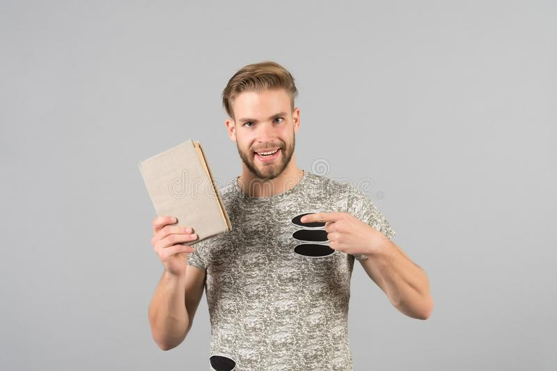 Mensen gebaarde ongeschoren kerel in modieus overhemd die op boek richten Mens het glimlachen het gezicht adviseert boek, grijze  royalty-vrije stock foto's