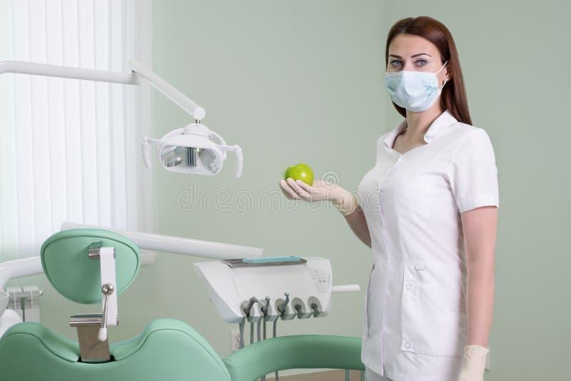 Mensen, geneeskunde, tandheelkunde en gezondheidszorgconcept - gelukkige jonge vrouwelijke tandarts met groene appel in hand op a royalty-vrije stock foto