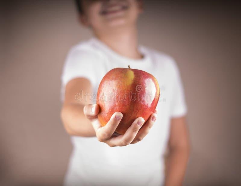 Mensen, gezond voedsel, kinderen en gelukconcept het kind geeft appel het glimlachen stock fotografie