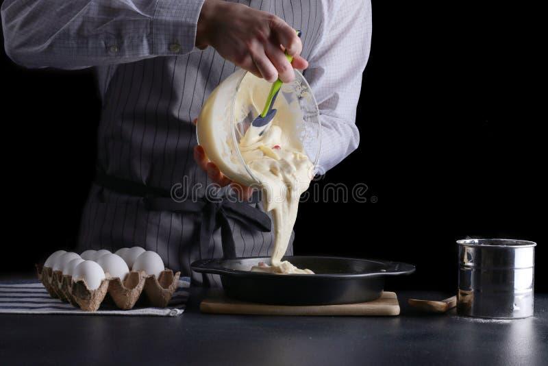 Mensen gietend deeg voor pastei cake die concept maken stock afbeeldingen