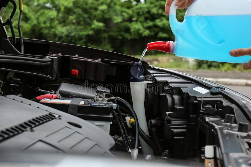 Mensen gietende vloeistof van plastic bus in het vloeibare reservoir van de autowasmachine, royalty-vrije stock foto