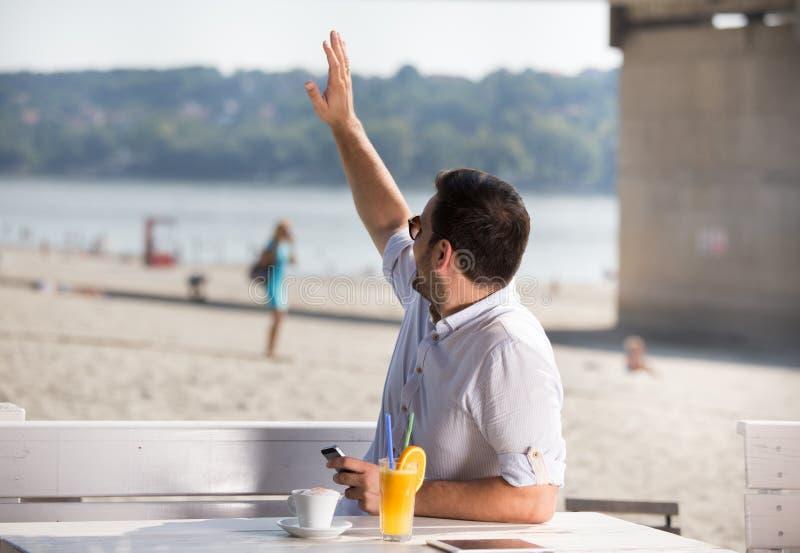 Mensen golvende hand aan een meisje op achtergrond in koffie op strand stock foto's