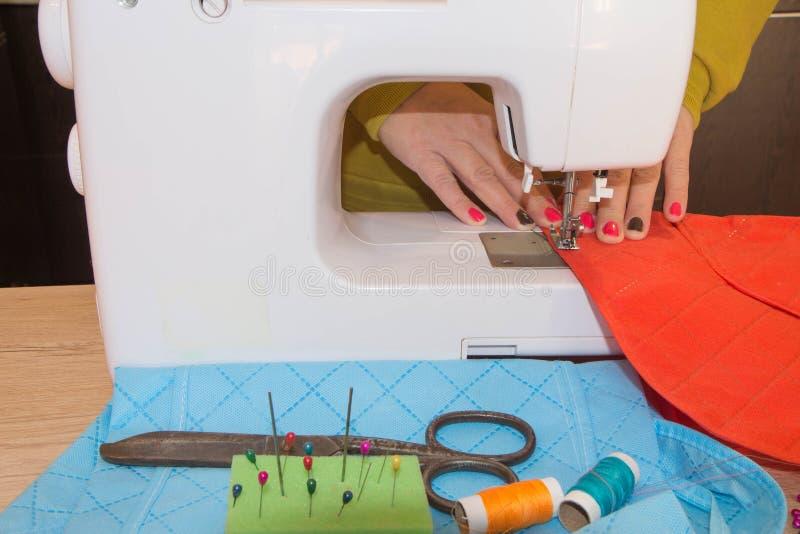 Mensen, handwerk, het naaien en het maken concept - de kleermakersvrouw met draad in naald stikkende stof voegt samen Kleren DE royalty-vrije stock fotografie