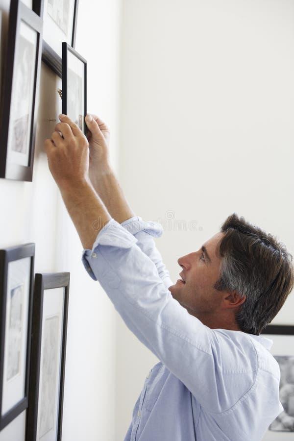 Mensen Hangende Omlijstingen op Muur thuis royalty-vrije stock foto