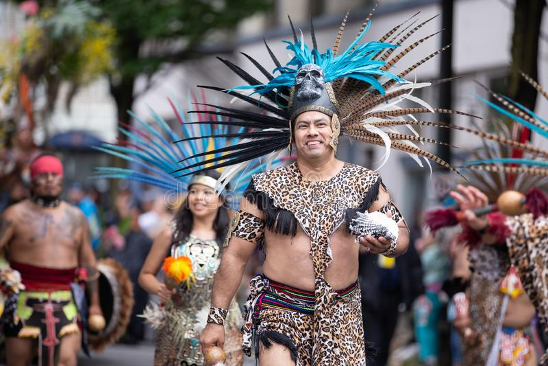 Mensen in het Azteekse kostuums marcheren stock afbeeldingen