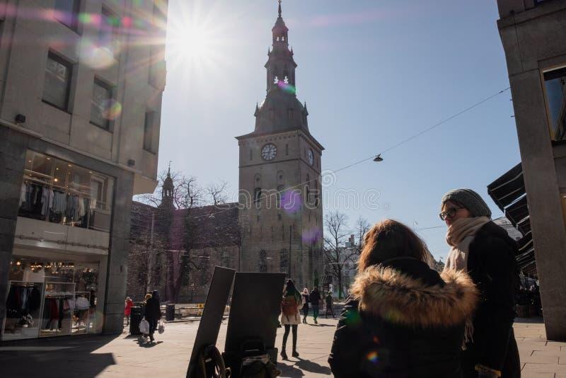 Mensen het lopen en activiteiten rond klokketoren in de stad van Oslo stock foto