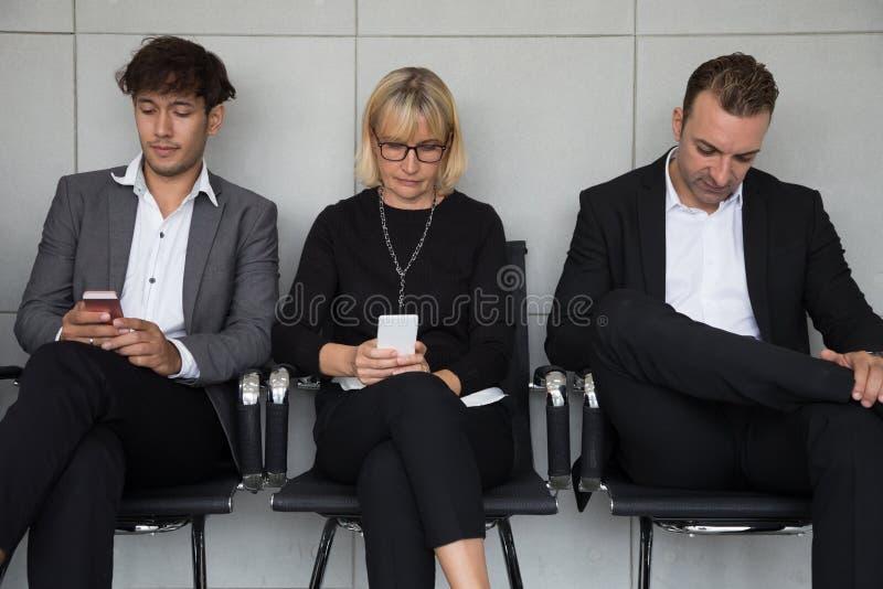 Mensen het zitten wachtend op een baangesprek en gebruikend sociale media toepassing op mobiele telefoon stock afbeelding