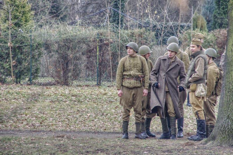 Mensen in historische militaire kostuums met helmen op hun hoofden royalty-vrije stock fotografie