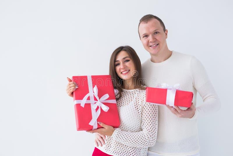 Mensen, Kerstmis, verjaardag, vakantie en de dagconcept van de valentijnskaart - gelukkige jonge man en vrouw met giftdozen op wi stock fotografie