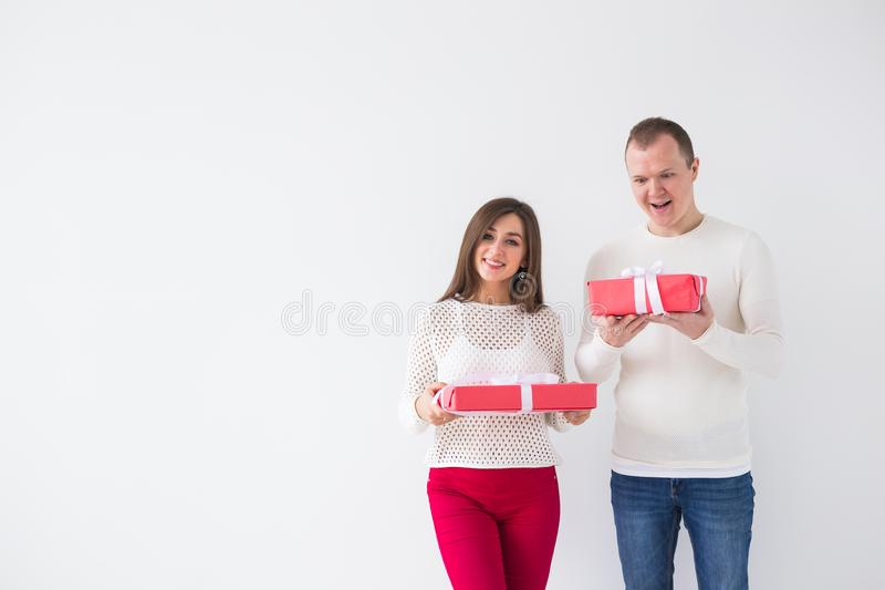 Mensen, Kerstmis, verjaardag, vakantie en de dagconcept van de valentijnskaart - gelukkige jonge man en vrouw met giftdozen op wi stock foto's