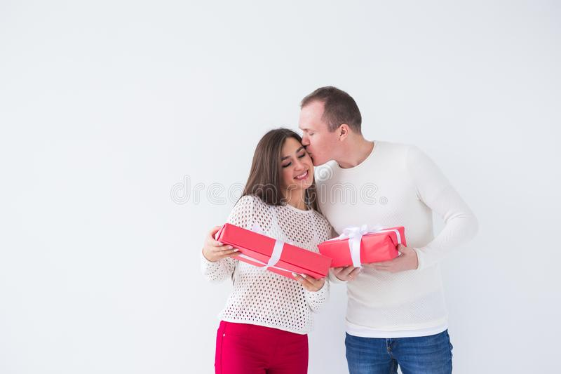 Mensen, Kerstmis, verjaardag, vakantie en de dagconcept van de valentijnskaart - gelukkige jonge man en vrouw met giftdozen op wi stock afbeeldingen