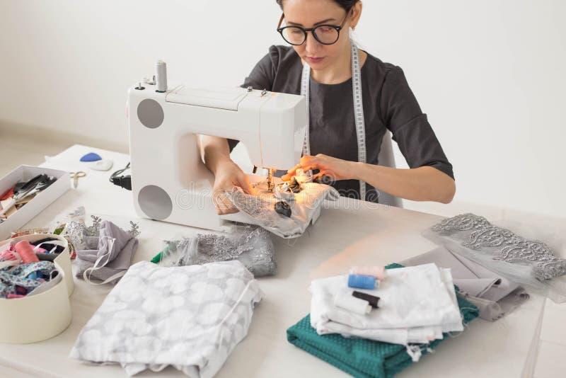 Mensen, kleermaker en manierconcept - jonge manierontwerper in haar werkplaats stock foto's