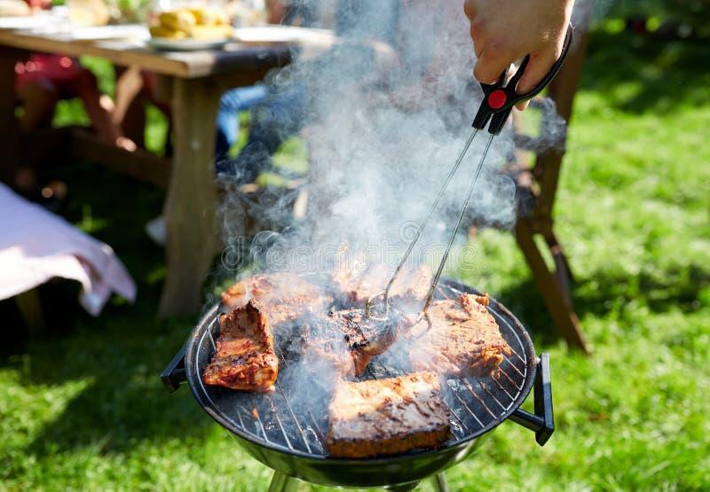 Mensen kokend vlees bij de barbecuegrill bij de zomerpartij stock afbeeldingen