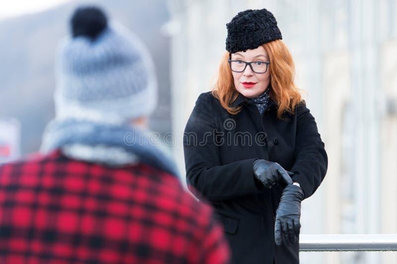 Mensen laat tot op heden Vrouwenafkeer om te wachten De kerel skiped tijd Bedrijfsvrouw verloren tijd De vrouw toont het horloge  royalty-vrije stock fotografie