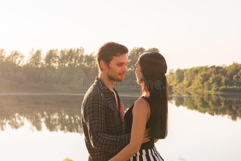 Mensen, liefde en aardconcept - Jonge mooie vrouw en knappe man die elkaar over waterachtergrond omhelzen stock afbeeldingen