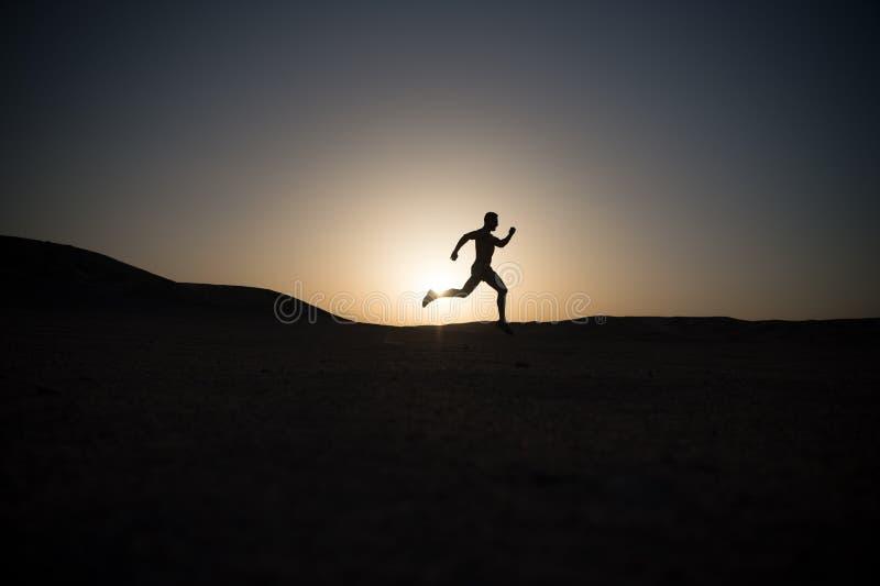 Mensen lopend silhouet bij zonsondergang, jonge Kaukasische looppas in berg stock fotografie