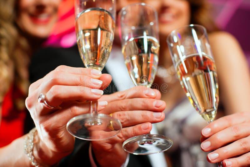 Mensen met champagner in een staaf royalty-vrije stock afbeeldingen