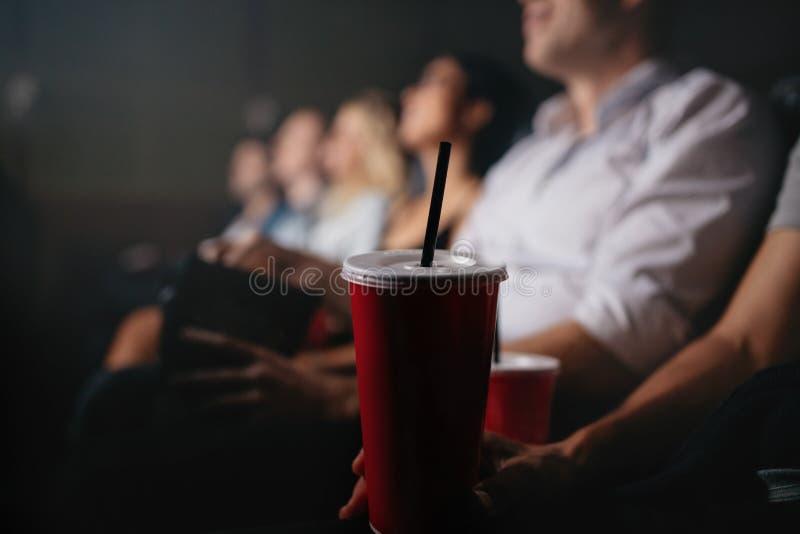 Mensen met frisdranken in bioscoop stock afbeelding