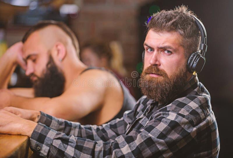 Mensen met hoofdtelefoons en smartphone het ontspannen bij bar Vermijd mededeling Vluchtwerkelijkheid Vrijdagontspanning in bar royalty-vrije stock afbeeldingen