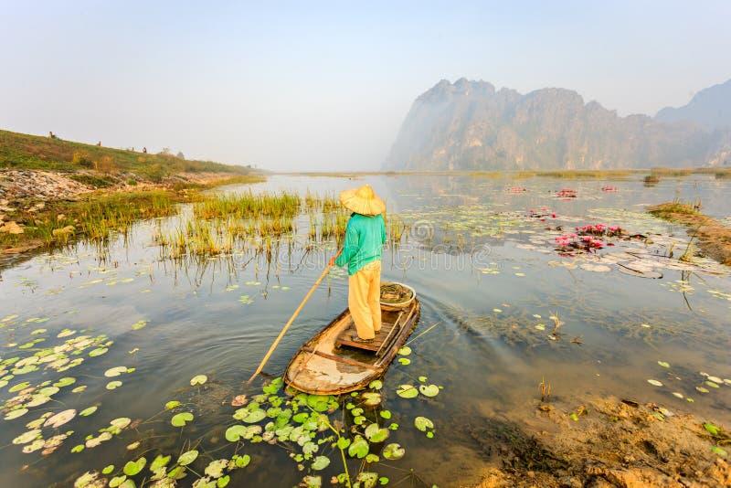 Mensen met kleine boot op Van Long-vijver, de provincie van Ninh Binh, Vietnam royalty-vrije stock afbeelding