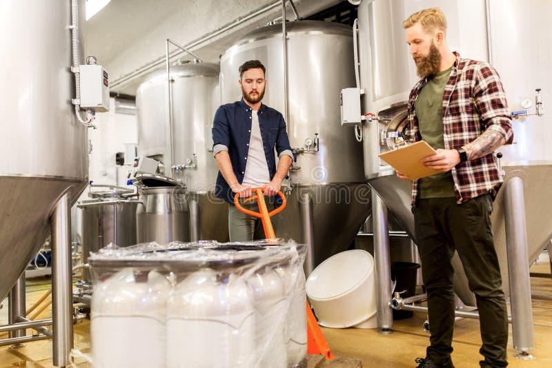 Mensen met mout en klembord bij de brouwerij van het ambachtbier stock fotografie