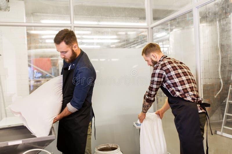 Mensen met moutzakken en molen bij de brouwerij van het ambachtbier stock fotografie