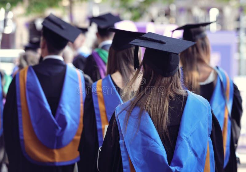 Mensen met universitaire diploma's bij Graduatieceremonie stock fotografie