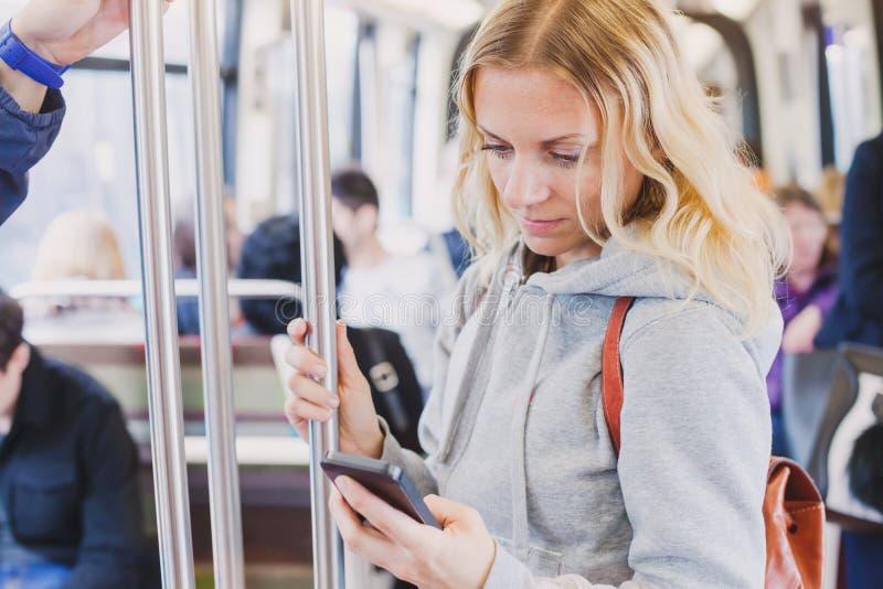 Mensen in metro, forenzen die, vrouwenpassagier het scherm van haar smartphone bekijken royalty-vrije stock fotografie