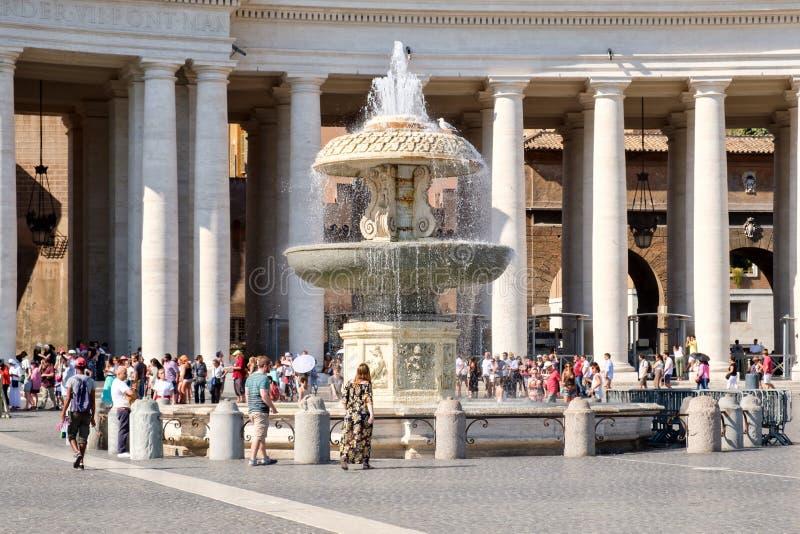 Mensen naast een fontein bij het Vierkant van Heilige Peter ` s in het Vatikaan stock foto