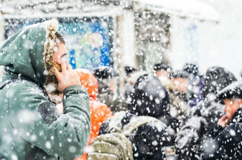 Mensen op bushalte in sneeuwval stock foto